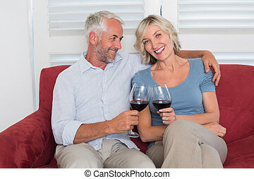 Happy relaxed mature couple toasting wine glasses in the...