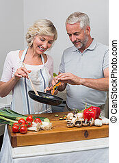Happy mature couple preparing food together in kitchen -...