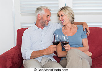 Relaxed mature couple toasting wine glasses in living room -...
