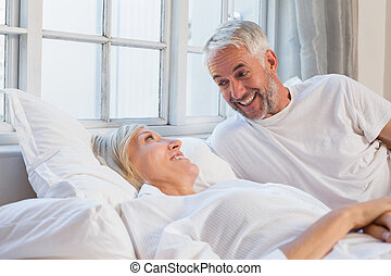 Smiling relaxed mature couple lying in bed - Portrait of a...