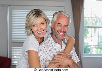 Portrait of a happy woman embracing mature man from behind...