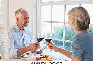 Happy mature couple toasting drinks over food by the window...