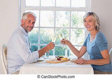 Side view portrait of a mature couple toasting drinks over...