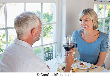 Portrait of a mature couple toasting wine glasses over food...