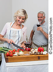 Man with wine glass and woman chopping vegetables in kitchen...