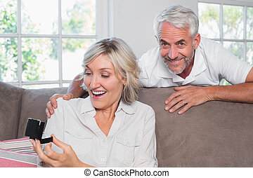 Smiling man surprising woman with a