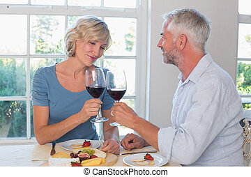 Mature couple toasting wine glasses over food - Portrait of...