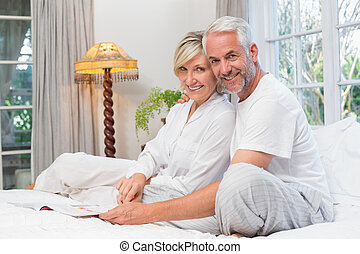 Portrait of a relaxed happy mature couple with book in bed -...