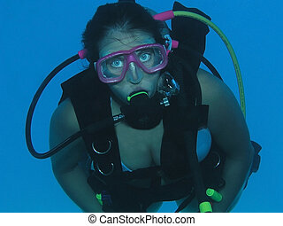 Woman scuba diving in the open water - A young woman scuba...