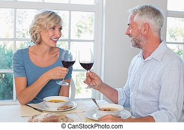 Happy mature couple toasting wine glasses over food against...