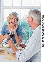 Happy mature couple toasting drinks over food against the...