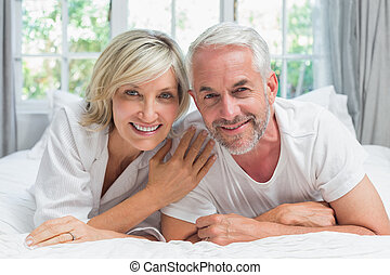 Happy mature couple lying in bed - Portrait of a happy...