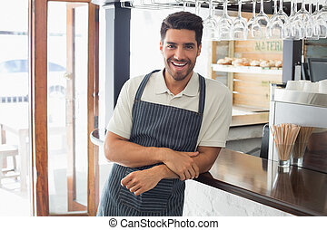 Portrait of a smiling young waiter at cafe counter