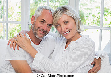 Loving happy mature couple with arm around sitting in bed at...