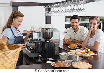 Couple with female cafe owner at coffee shop