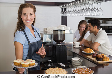 Portrait of a smiling female cafe owner holding sweet snacks with couple at counter in the coffee shop