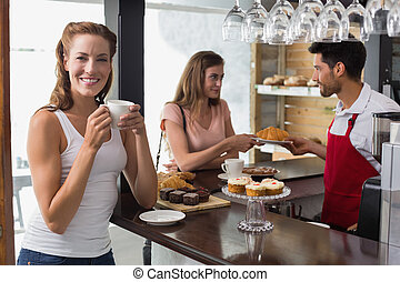 Smiling woman drinking coffee with friend and male barista at counter in the coffee shop