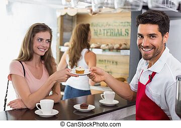 Barista giving pastry to woman at counter in coffee shop -...