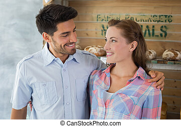 Couple with arm around at bakery - Portrait of a loving...