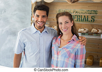 Couple with arm around at the bakery - Portrait of a loving...