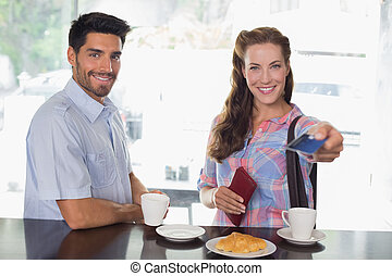 Couple with woman holding out credit card at coffee shop