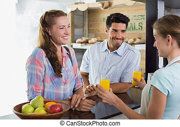 Waitress giving orange juice to a couple at coffee shop -...