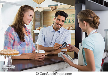 Couple paying bill at coffee shop using card bill