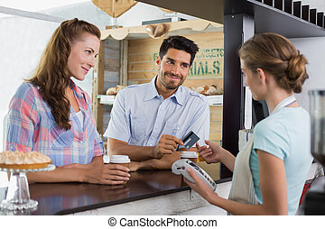 Couple paying bill at coffee shop using card bill - Side...