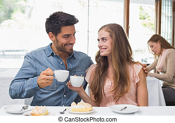 Smiling couple having coffee at coffee shop