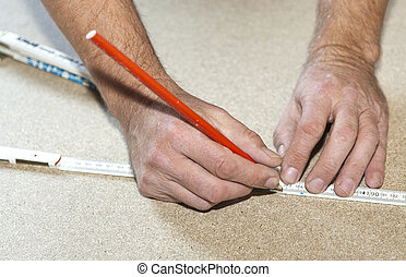 man uses a yardstick to mark the chip board - man uses a...
