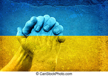Hands on Ukrainian Flag - Mature Hands in Pray Gesture on...
