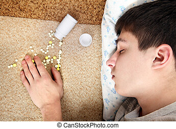 Teenager sleeps near the Pills on the Bed at the Home