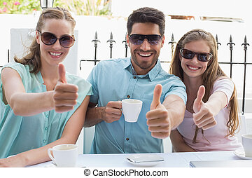Happy friends gesturing thumbs up in café