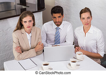 Business people using laptop together at office desk