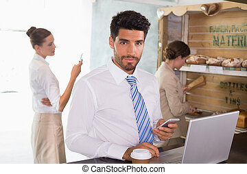 Businessman using mobile phone and laptop in office...
