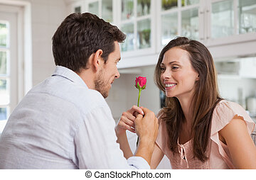 Man giving a rose to a happy woman