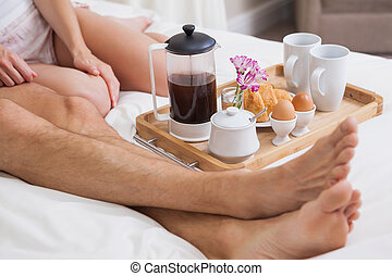 Low section of couple having breakfast in bed - Low section...