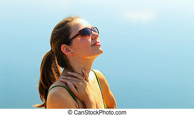 Soaking up the Sun - A young woman in a bikini soaks up the...