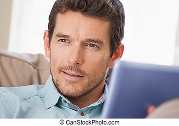 Man with digital tablet looking awa - Close-up of a young...
