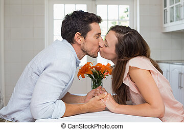 Side view of a loving couple kissing in kitchen - Side view...