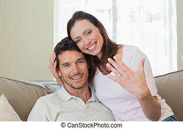 Happy woman showing engagement ring besides man - Portrait...