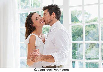 Loving young man kissing woman - Side view of a loving young...