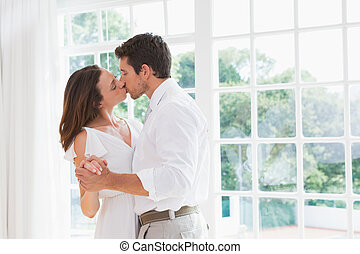 Loving young couple kissing - Side view of a loving young...