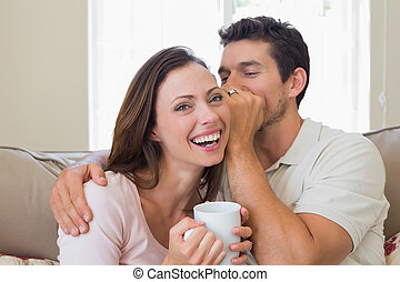Man whispering secret into a cheerful womans ear in living...