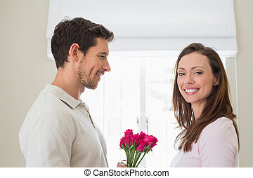Side view of man giving happy woman flowers