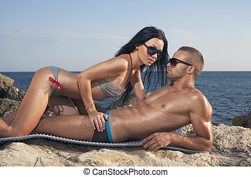 Couple lies on beach. Girl kissing guy