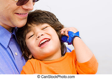 Father and son laughing together on beach Child has cerebral...
