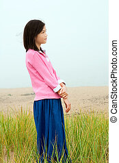 Young girl quietly standing on misty foggy field - Young...