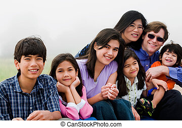 Multiracial family of seven sitting on beach