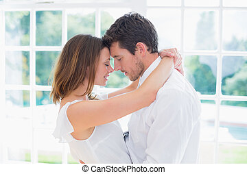 Loving young couple with arms around - Side view of a loving...